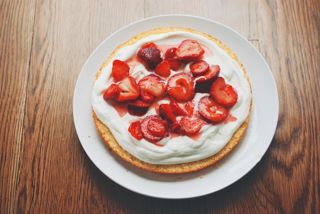 spreading and strawberries cream across cake